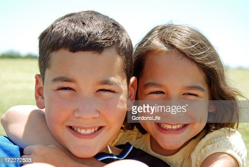 A smiling young brother and sister posing outdoors