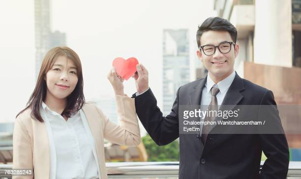 Smiling Young Business Couple Holding Red Paper Heart Shape