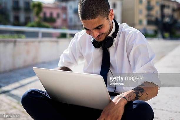 Smiling young businessman looking at laptop
