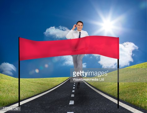 Smiling young businessman running on a road with copy space banner : Stock Photo