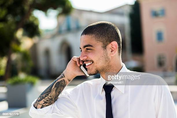 Smiling young businessman telephoning with smartphone