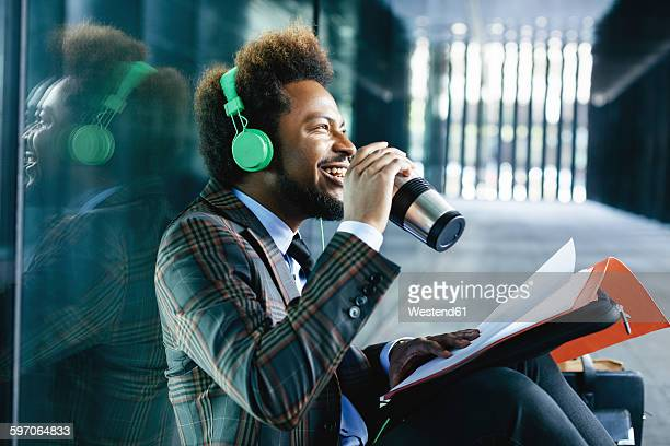 Smiling young businessman with coffee to go mug, headphones and folder outdoors