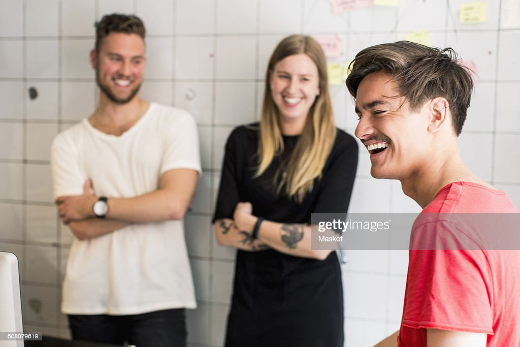 Smiling young businessman with colleagues in background at new office