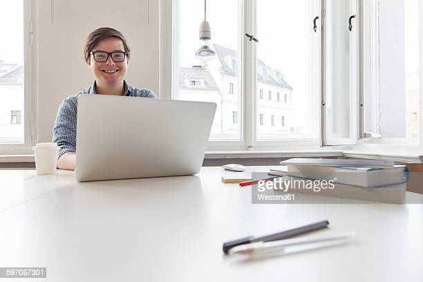 Smiling young businesssman using laptop in a modern office