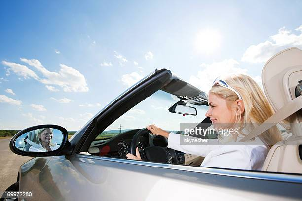 Smiling young businesswoman driving a convertible