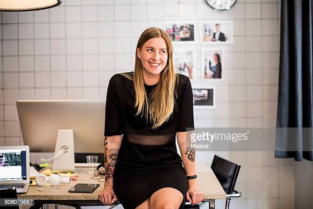 Smiling young businesswoman leaning at table in new office