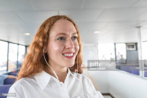 Smiling young businesswoman listening to earphone music on passenger ferry