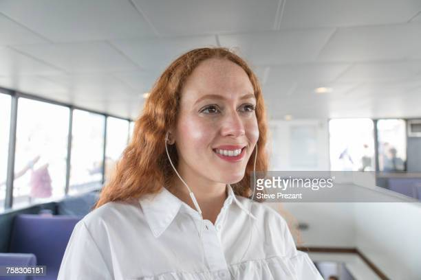Smiling young businesswoman listening to earphones on passenger ferry