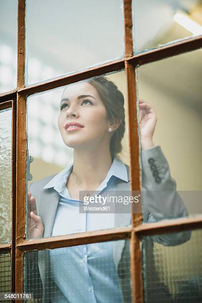 Smiling young businesswoman looking out of window