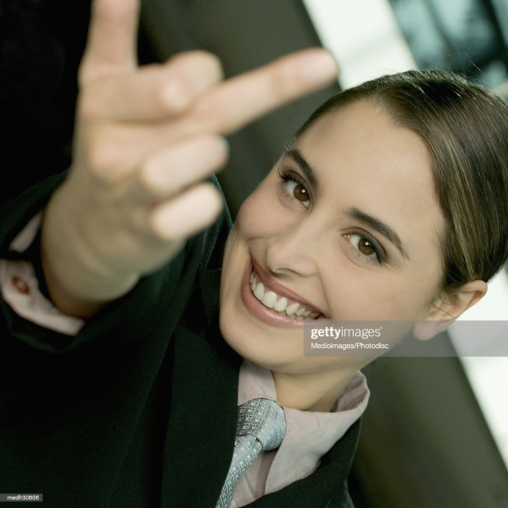 Smiling young businesswoman making obscene gesture with finger, close-up, tilt : Stock Photo