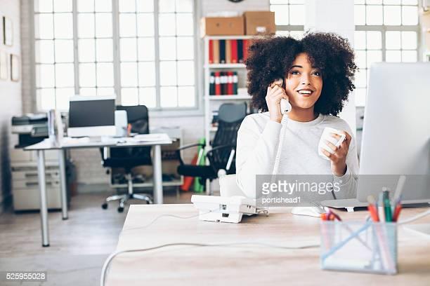 Lächelnde junge Geschäftsfrau spricht am Telefon am Arbeitsplatz