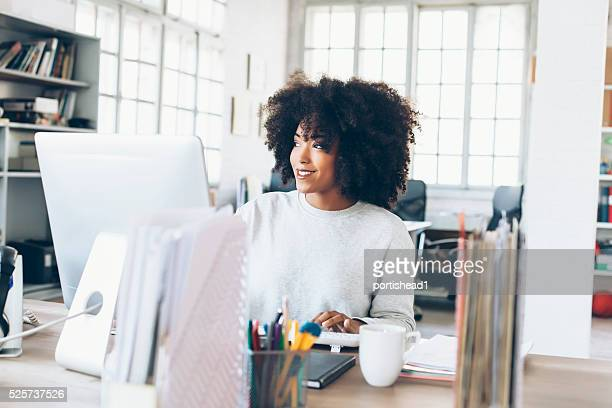 Smiling young businesswoman using computer at the office
