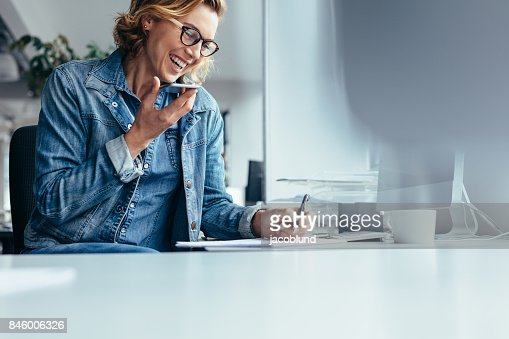 Smiling young businesswoman working at her desk : Foto de stock
