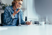 Young female executive working in office. Smiling young businesswoman talking on cellphone and writing notes.
