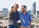 Smiling young caucasian friends making selfie in front of city skyline as travel and friendship concept