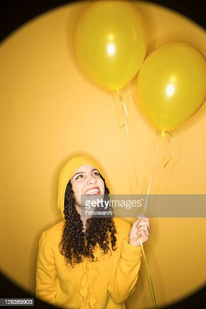 Smiling young Caucasian woman with balloons wearing yellow raincoat on yellow background.