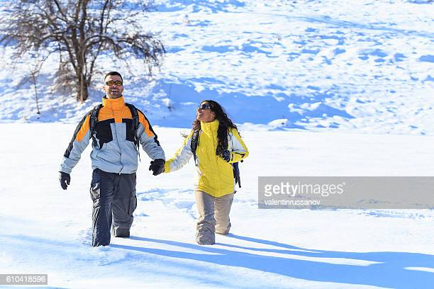 Smiling young couple backpackers hiking in the snow