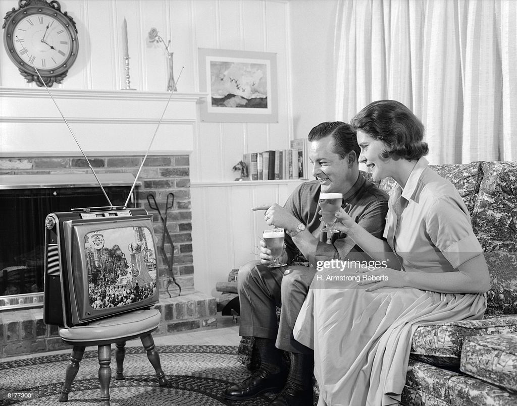 Smiling Young Couple Both Sitting On A Sofa With A Glass Of Beer In Thier Hands Watching A Portable Tv Thats Sitting On A Stool In The Living Room. : Stock Photo