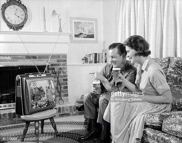 Smiling Young Couple Both Sitting On A Sofa With A Glass Of Beer In Thier Hands Watching A Portable Tv Thats Sitting On A Stool In The Living Room.