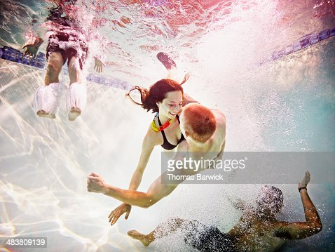 Smiling young couple embracing underwater : Stock Photo