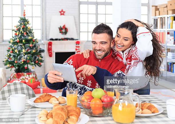 Smiling young couple having fun on christmas breakfast at home