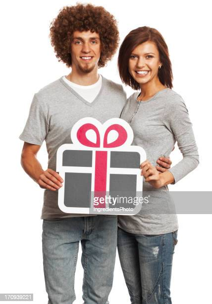 Smiling young couple holding gift sign isolated on white background.