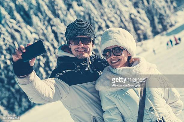 Smiling Young Couple how Taking Selfie at Snowy Mountains