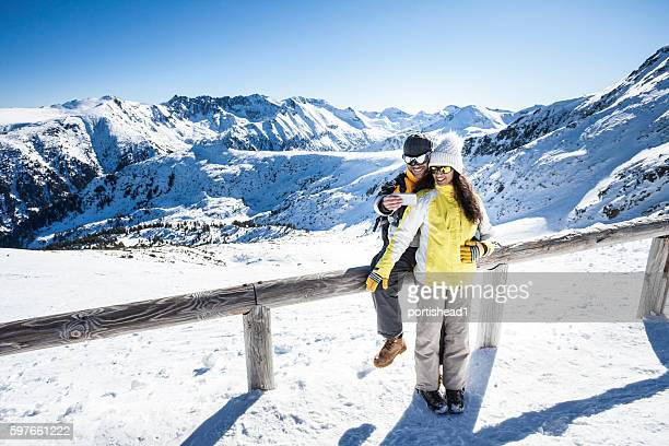 Smiling young couple making selfie in the snow mountain