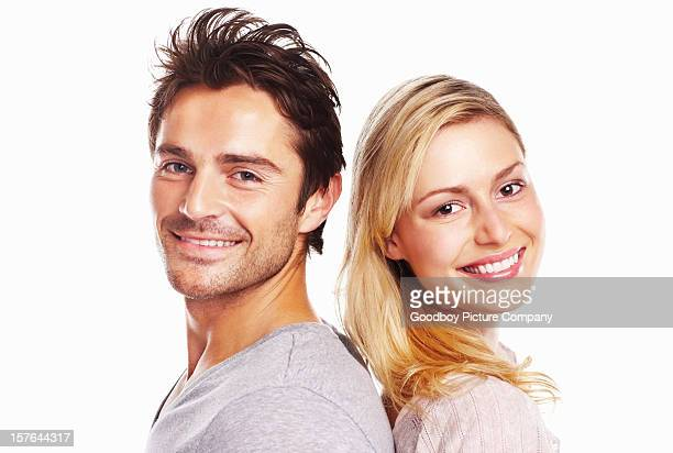 Smiling young couple standing against white background