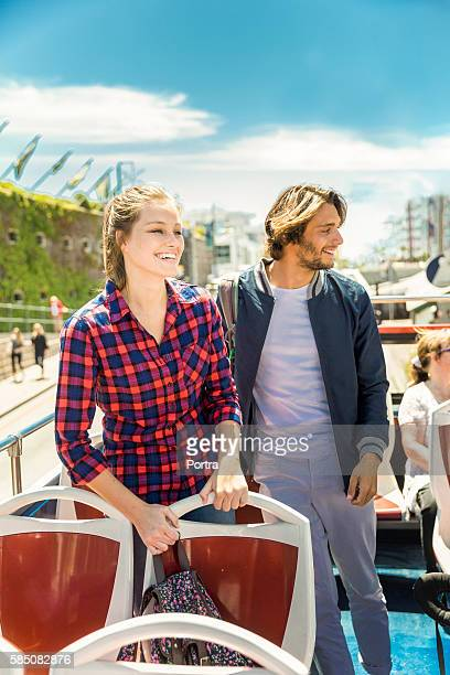 Smiling young couple standing in tour bus in city