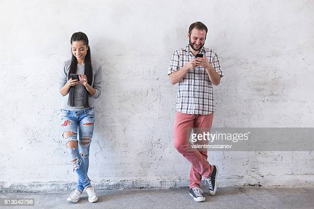 Smiling young couple using smart phones at new empty home