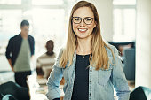 Young designer wearing glasses and smiling confidently while standing in an office with colleagues working behind her