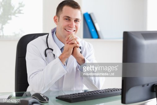Smiling doctor sitting at his desk : Stock-Foto