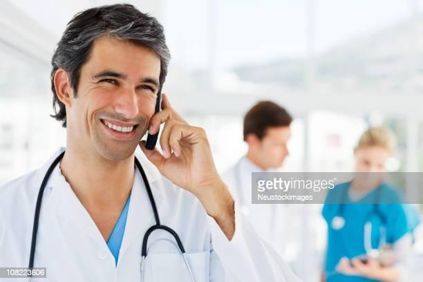 Lächelnd Junger Arzt sprechen auf cellphone mit Kollegen im Hintergrund