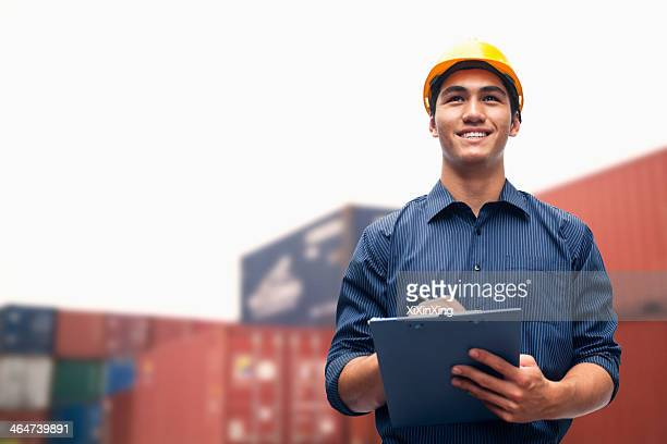 Smiling young engineer in protective work wear in a shipping yard examining cargo