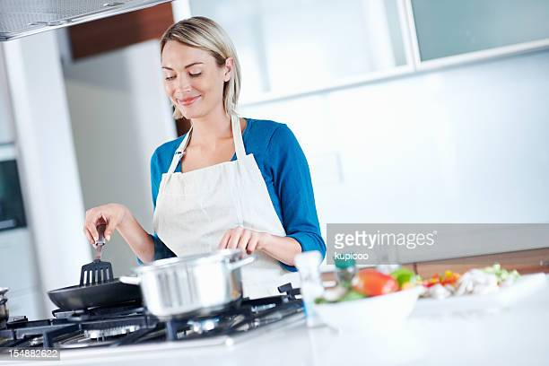 Smiling, young female cooking food in the kitchen