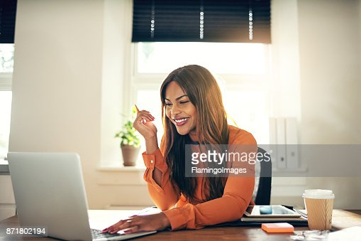 Smiling young female entrepreneur working on a laptop at home : Stock Photo