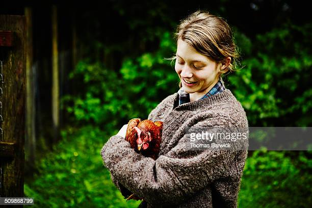 Smiling young female farmer holding chicken