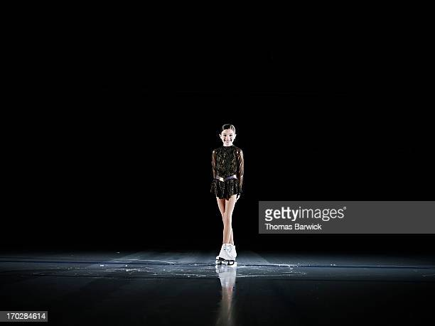 Smiling young female figure skater standing on ice