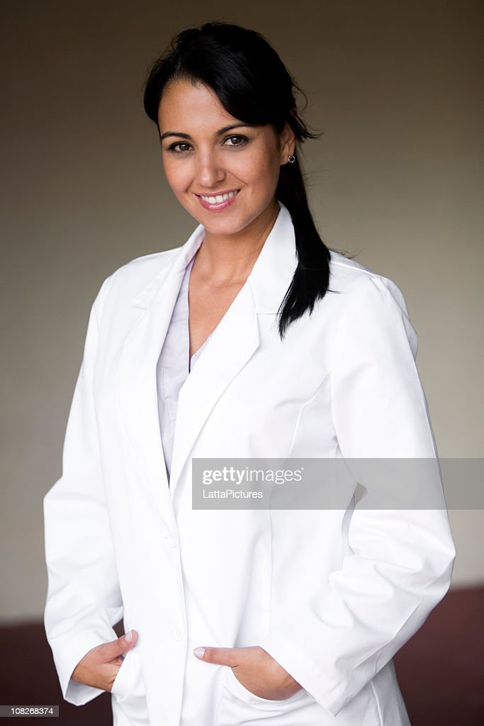 Smiling young female in lab coat : Stock Photo