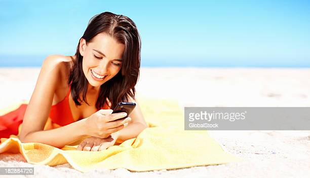 Smiling young female using cellphone on the beach