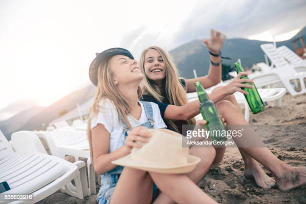 Smiling Young Females Sitting on Sand and Drinking Beer at Beach