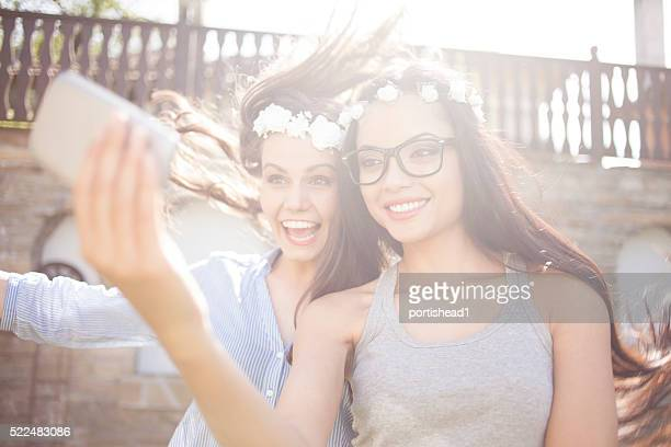 Smiling young friends with wreath making selfie