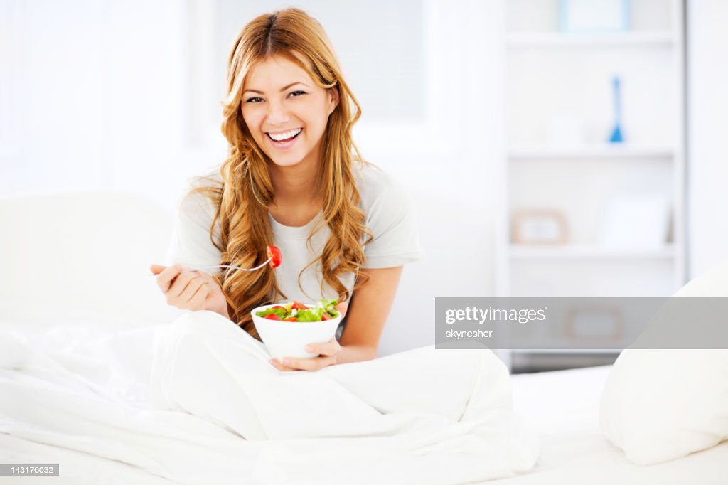 Smiling young girl eating salad for breakfast. : ストックフォト