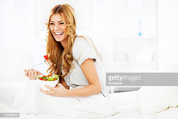 Smiling young girl eating salad for breakfast.