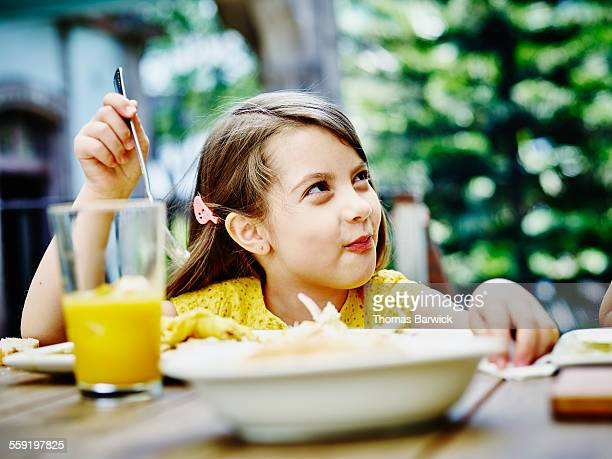 Smiling young girl enjoying lunch at outdoor table