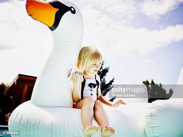 Smiling young girl floating on inflatable pool toy