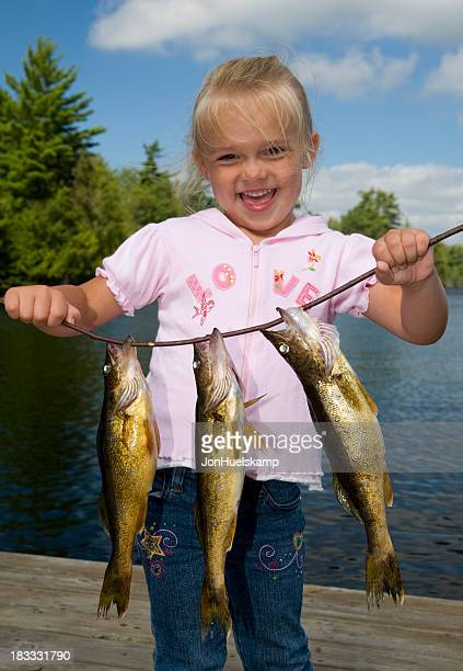 Smiling young girl holding a line with three fish
