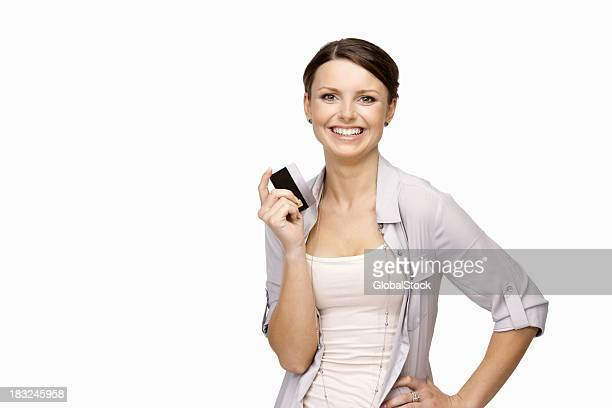 Smiling young girl holding credit card against white background