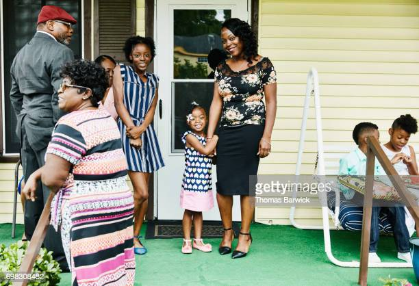 Smiling young girl holding mothers hand on front porch of home